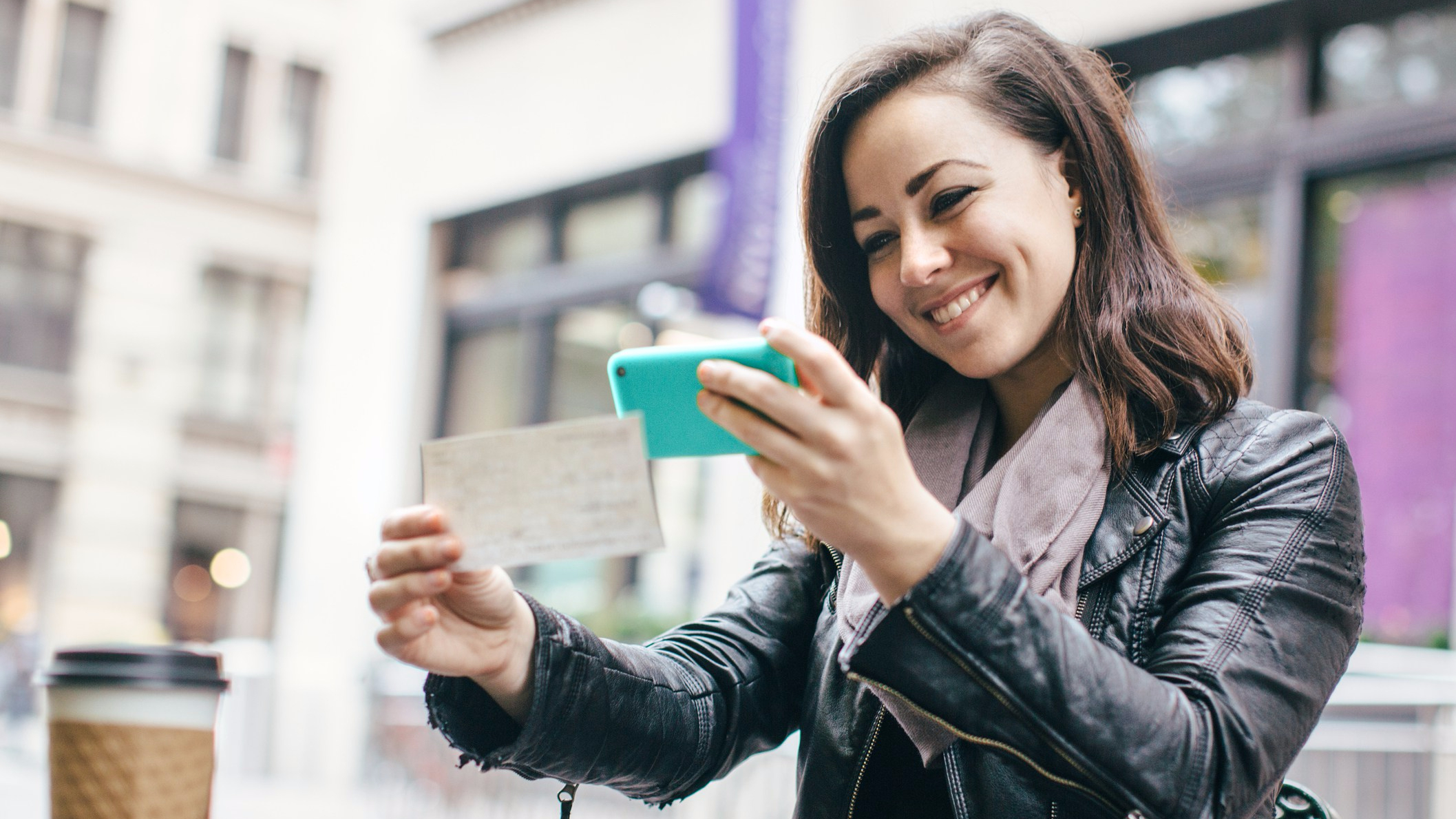 young woman depositing her check with her mobile phone