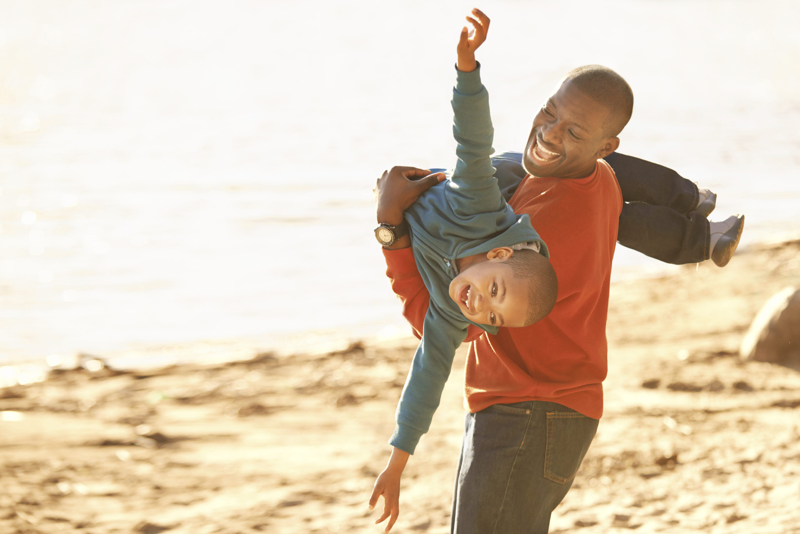 father at the beach with young son, playing airplane