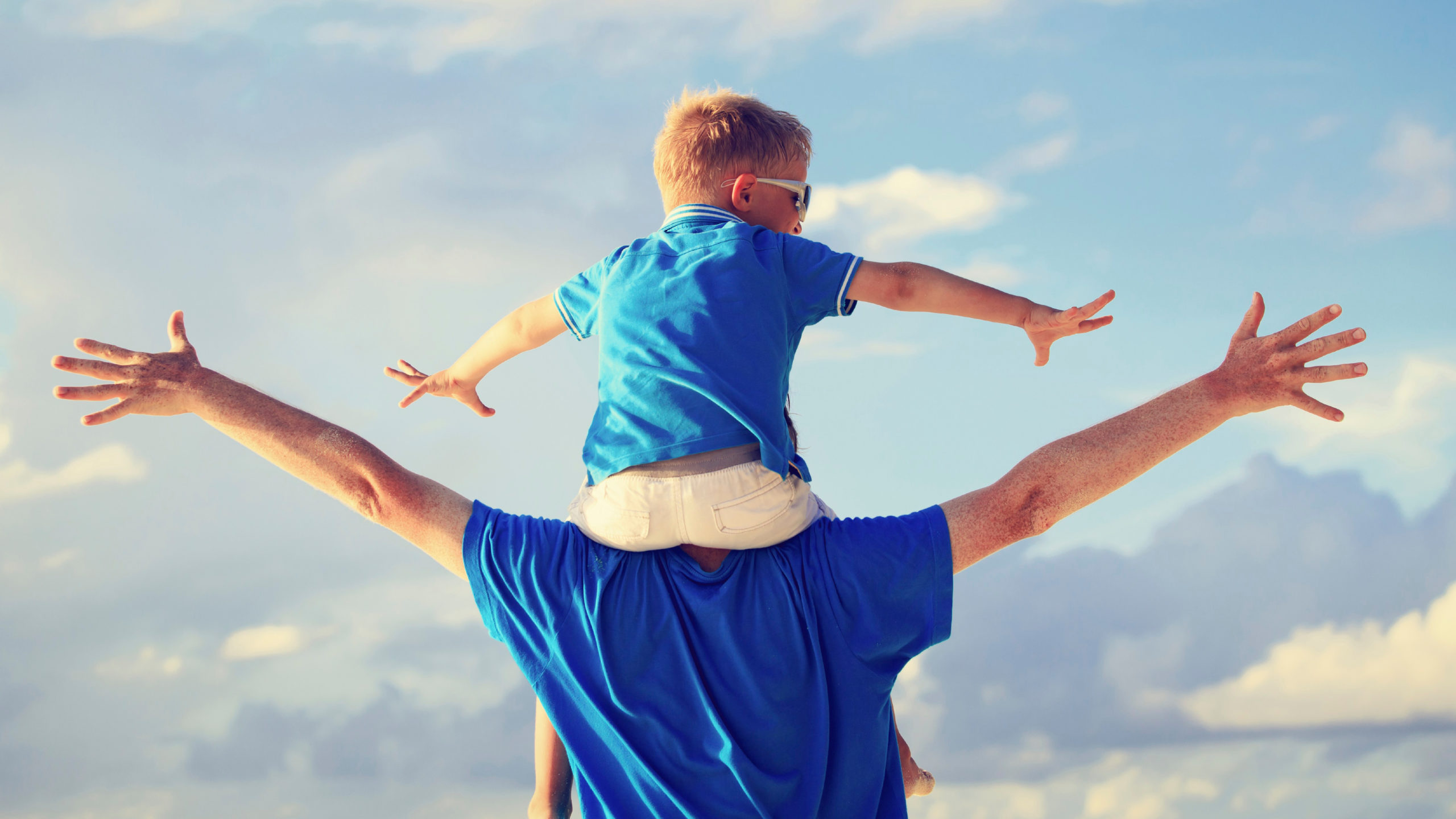 father holding toddler son on his shoulders