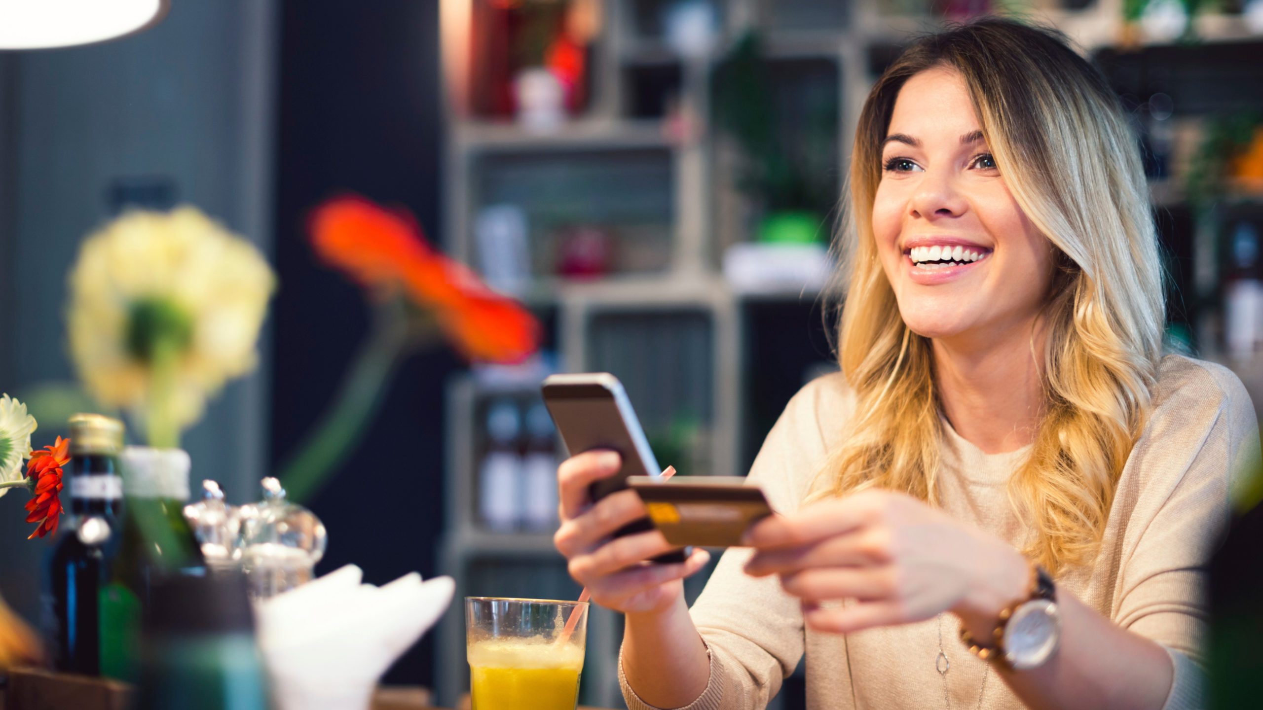 Smiling woman reading text messages over dinner in a bistro