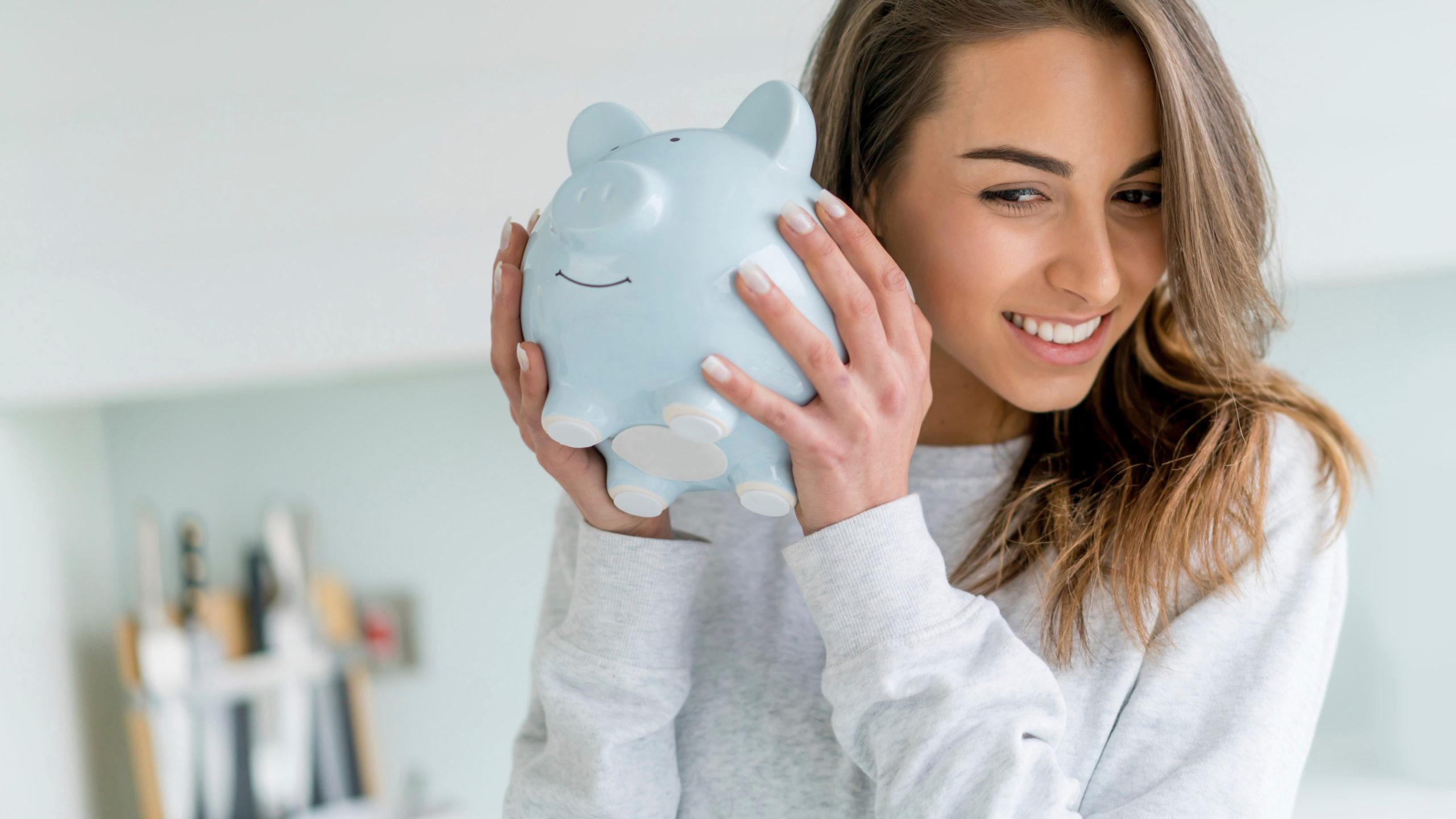 female teenager shaking piggy bank