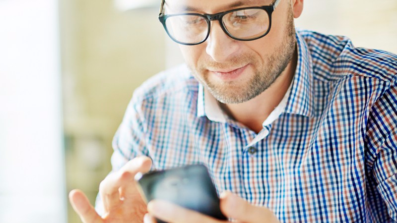 Mature businessman writing sms in office